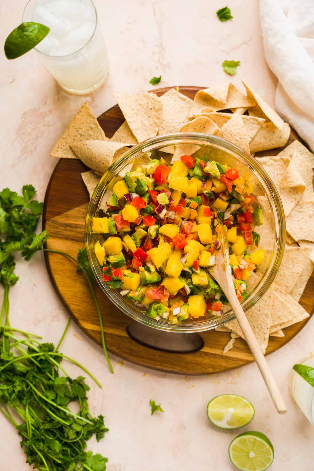 Bowl of chunky mango salsa with avocados with chips and cilantro on the side.