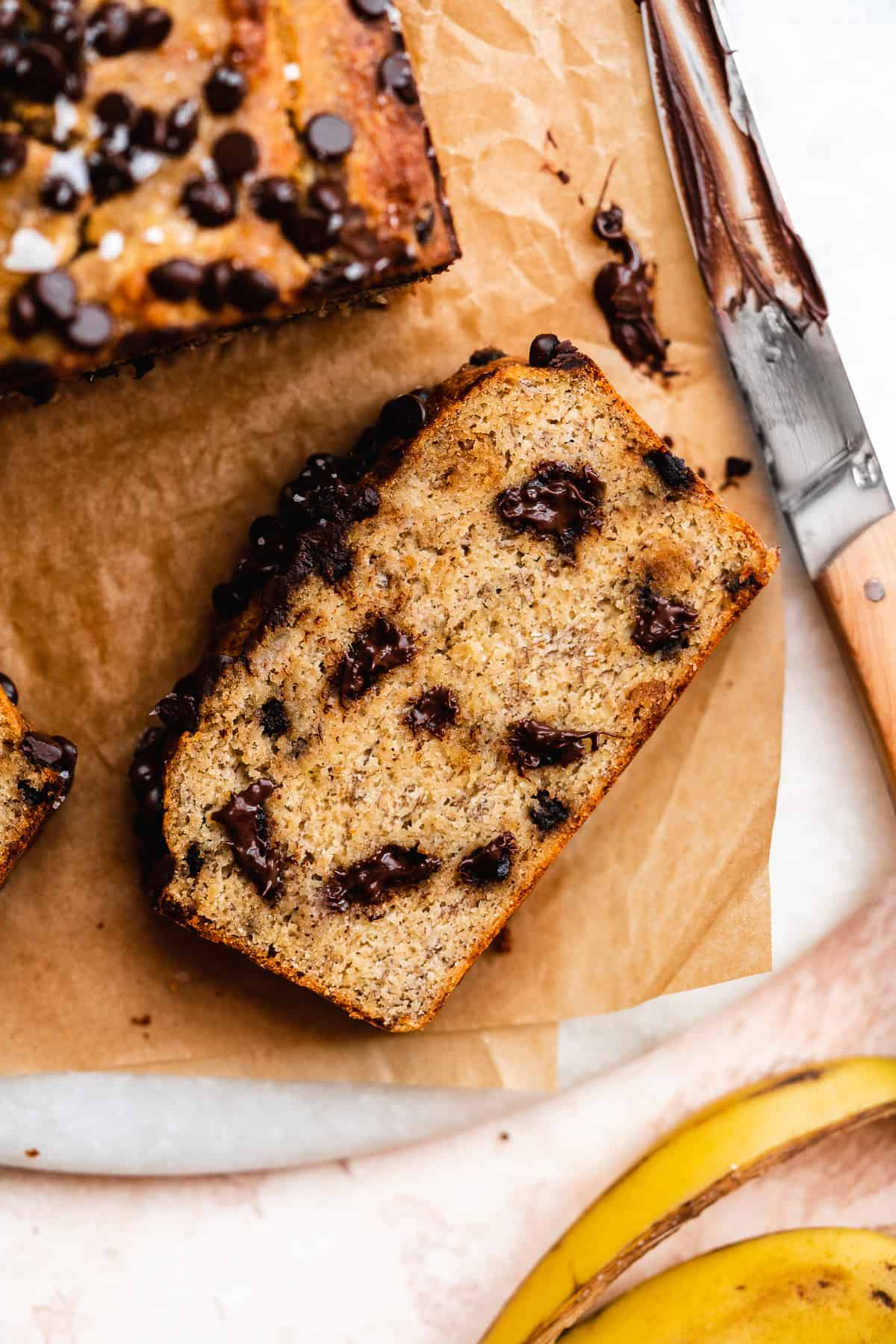 A slice of banana bread with chocolate chips on brown parchment paper with a knife to the side.