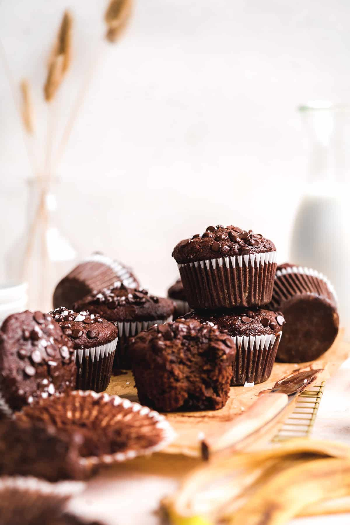 Chocolate muffins stacked on top of each other and scattered on cooling rack.