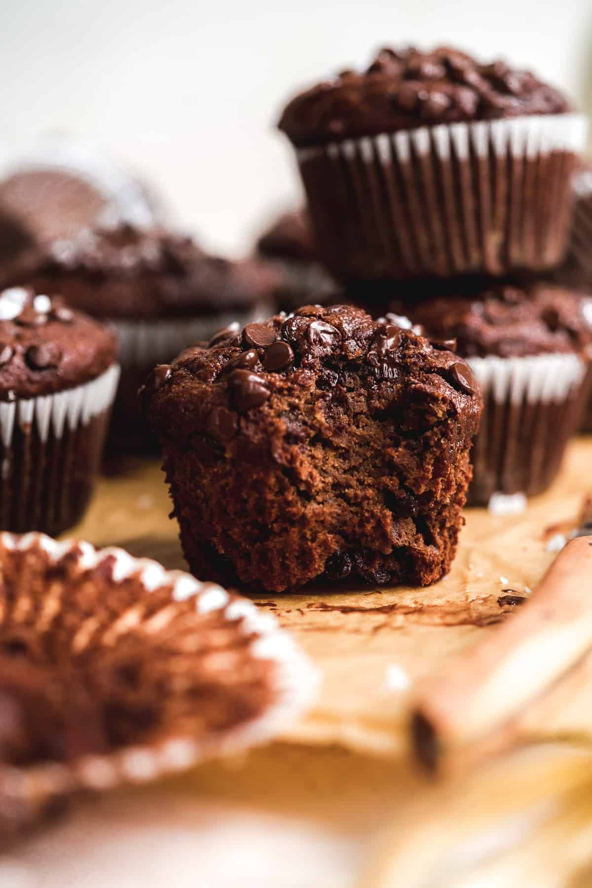 Up close view of chocolate muffin with a bite taken out of it on brown parchment paper.