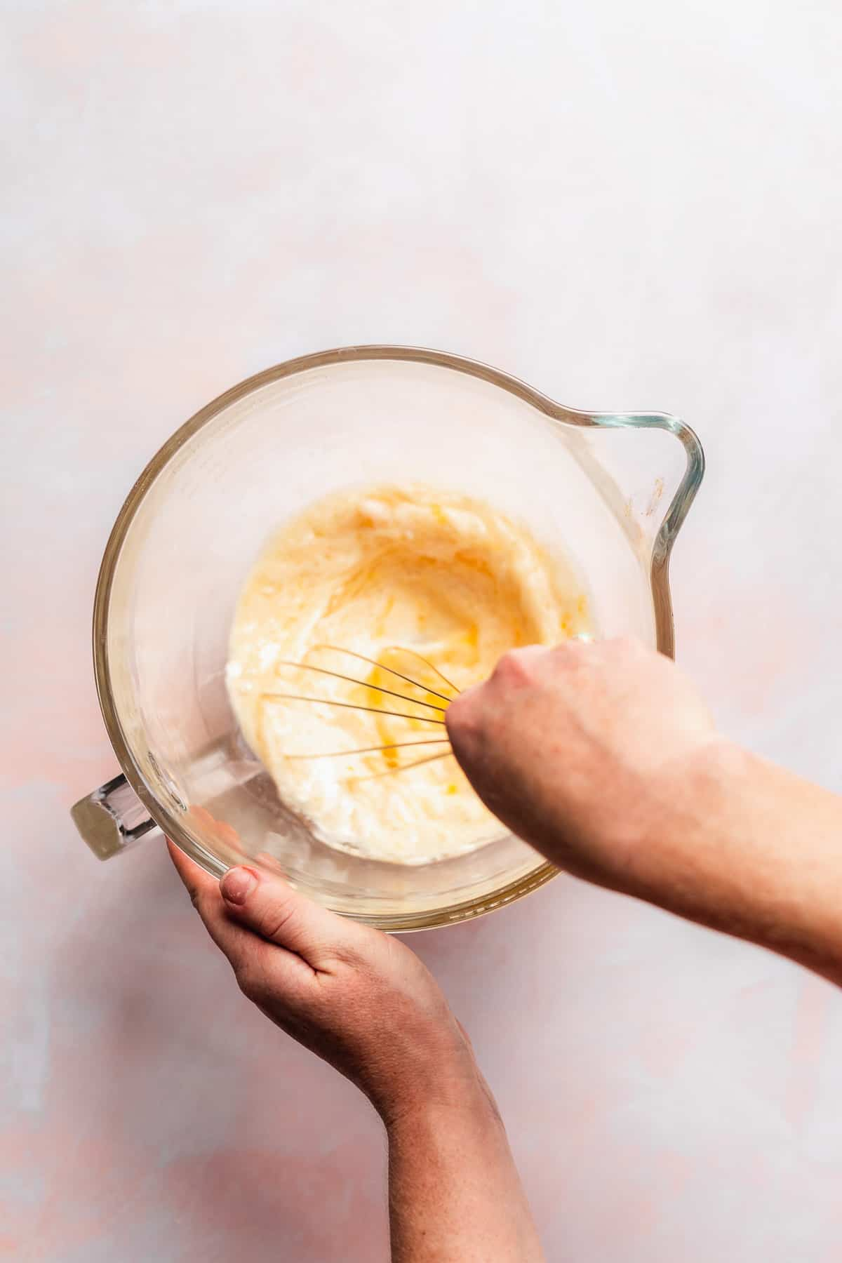 Person whisking a mixture in a glass mixing bowl.