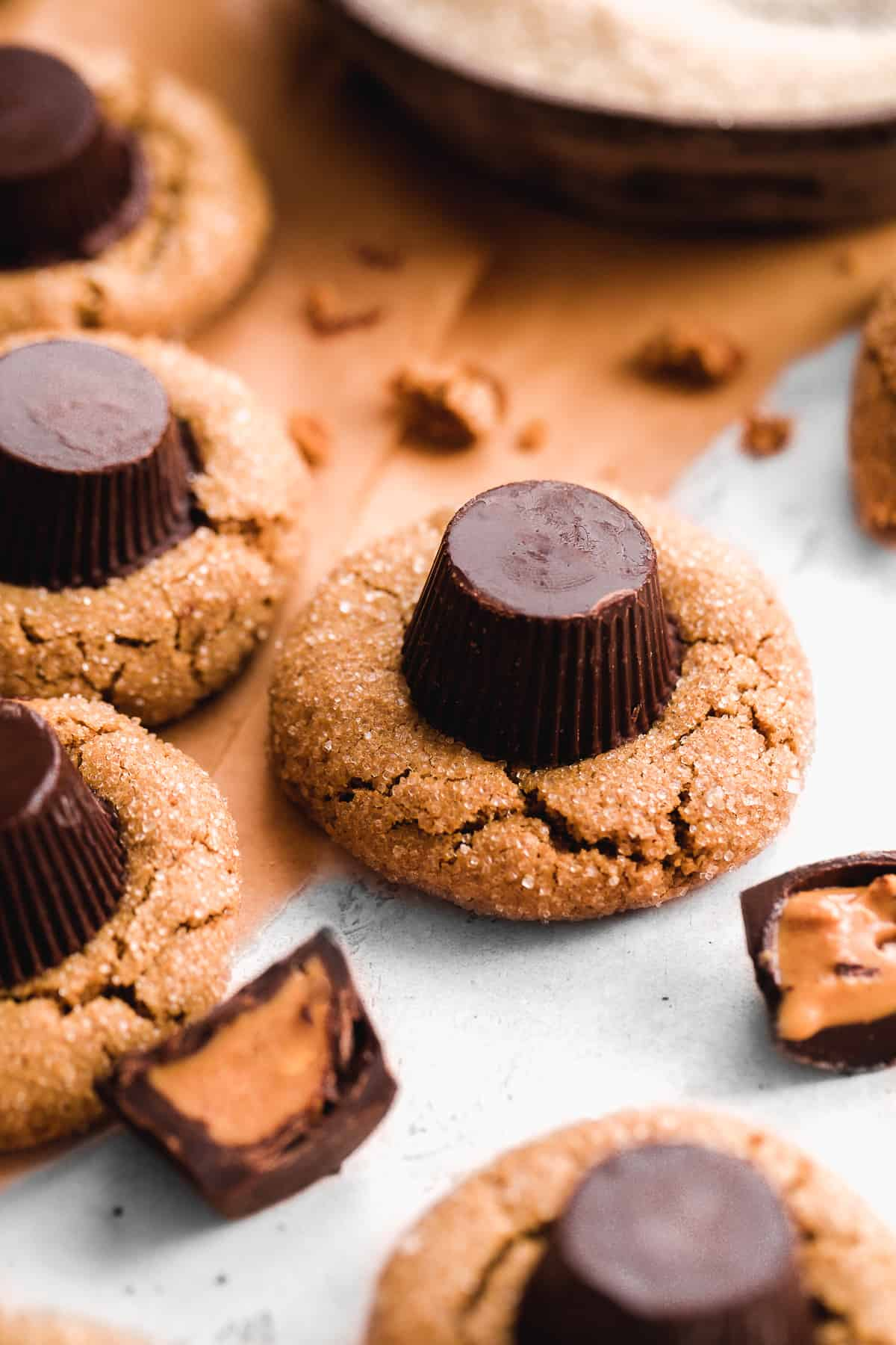 Cookies with a peanut butter cup on top and sugar coating scattered on a surface.