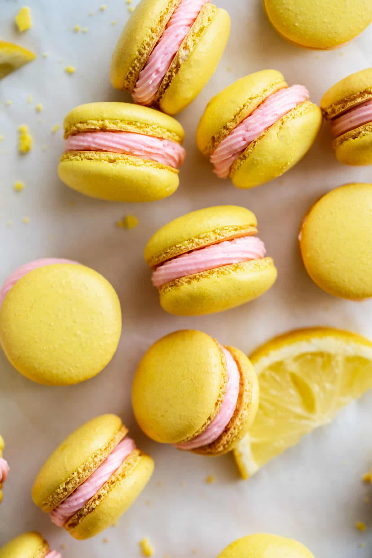 Pink lemonade macarons scattered on a white surface.