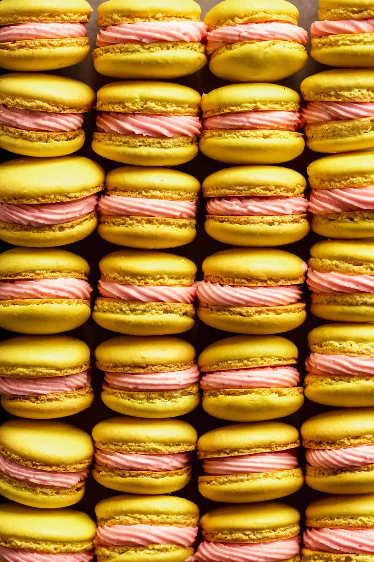 Lemonade macarons with pink icing lined up in rows.