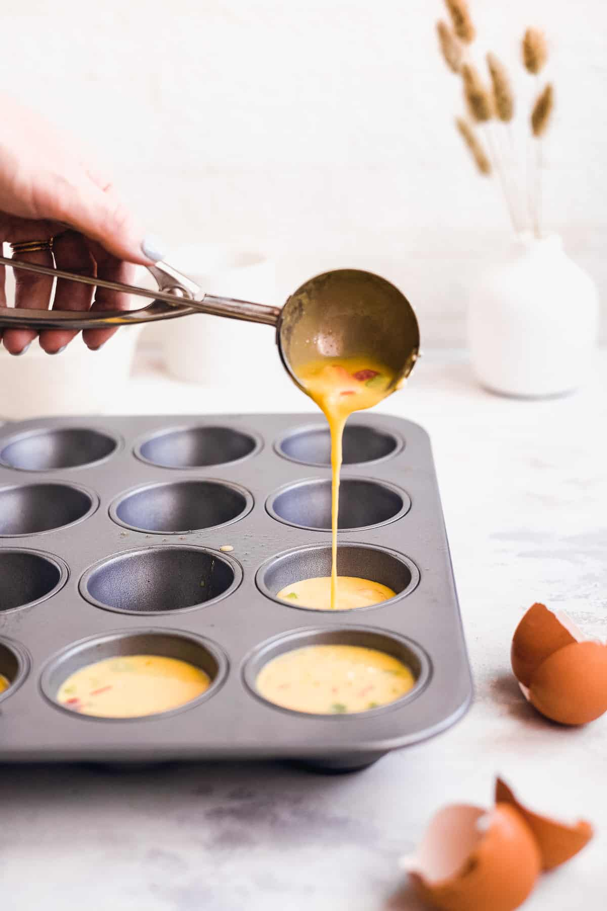 Hand pouring egg batter into a muffin tin.