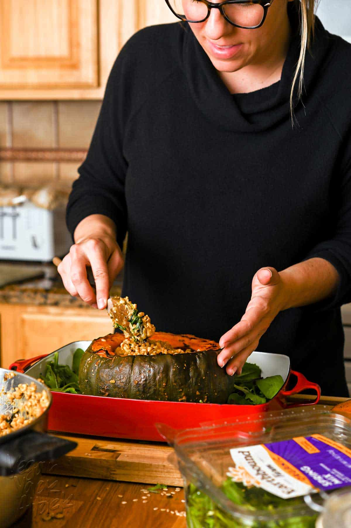 A woman in a black, long sleeve shirt, spooning rice stuffing into a large, roasted squash, that is in a red casserole dish.