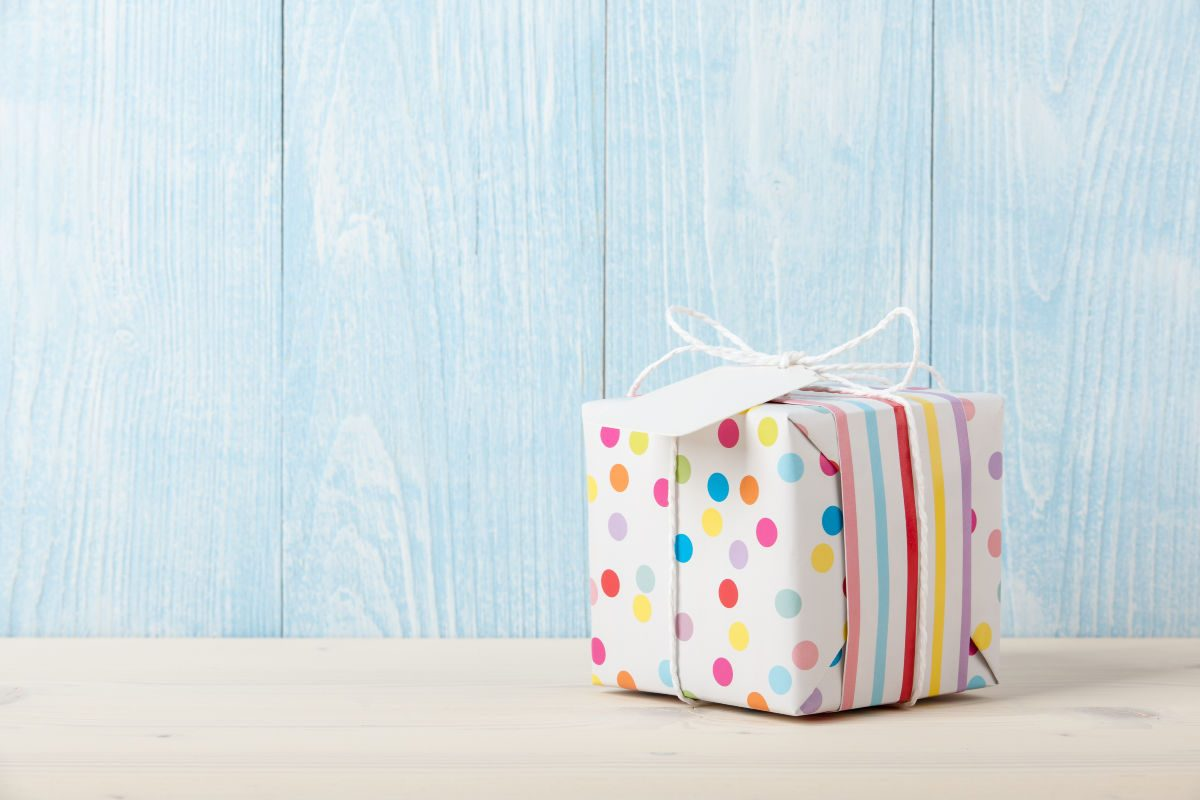 gift ideas for kids- single wrapped gift on a table with a blue wooden background