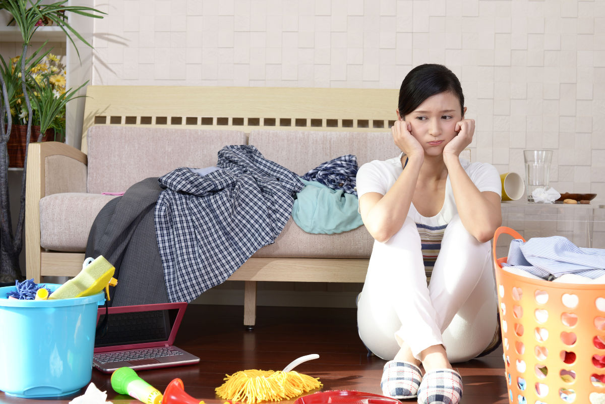 stressed woman sitting on floor surrounded by clutter