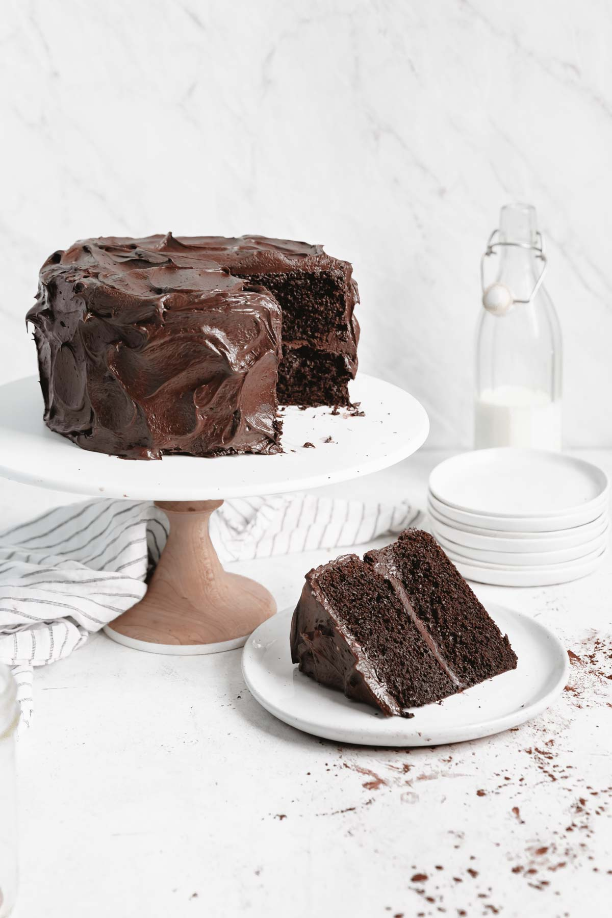 chocolate cake on a cake stand with a slice taken out