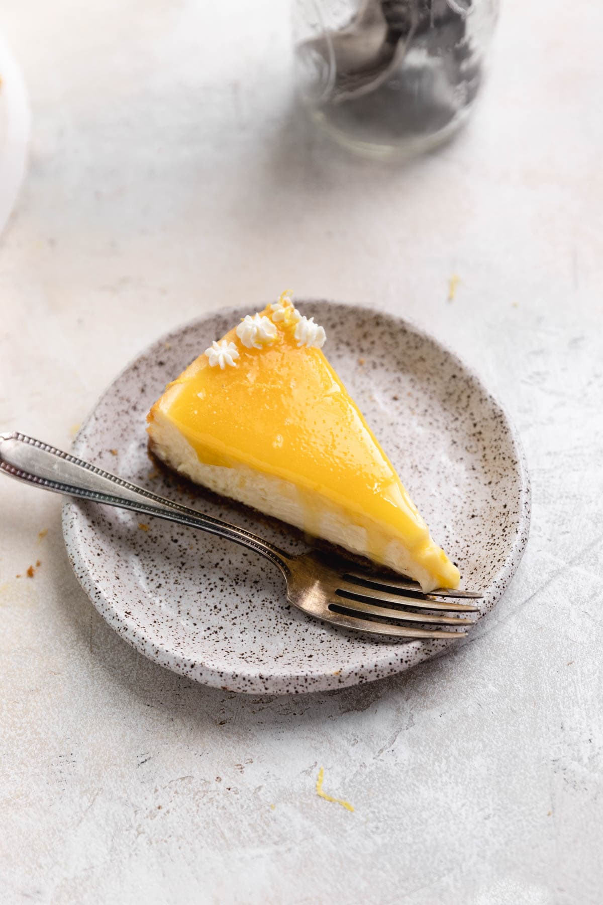 slice of lemon cheesecake topped with lemon curd
