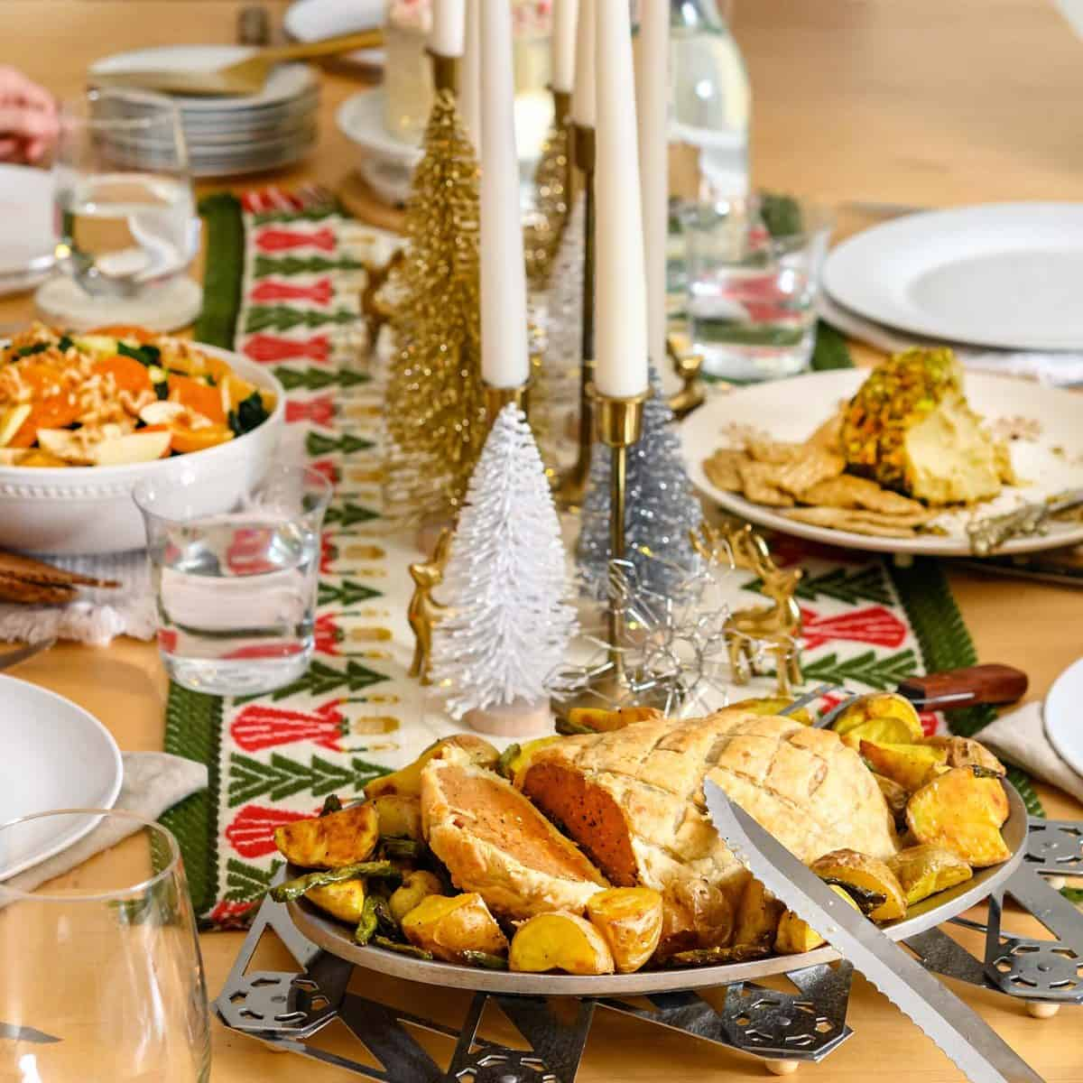 Image of an ultimate vegan holiday dinner spread with table runner and dishes, including salad and sliced seitan Wellington