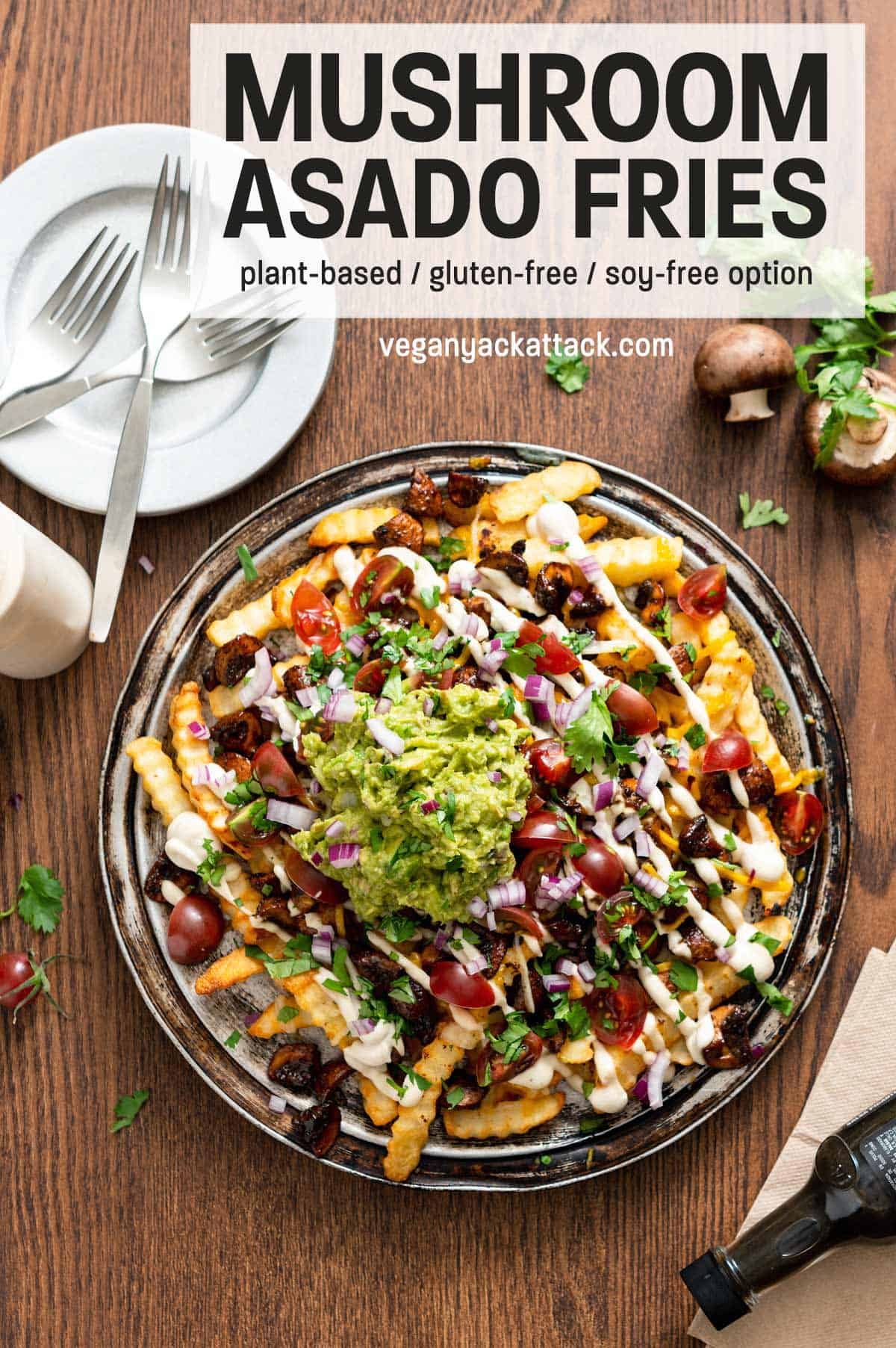 Platter of vegan mushroom asado fries on a wood table, with plates and forks