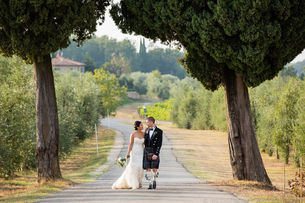 bride and groom walking on a Tuscan country road