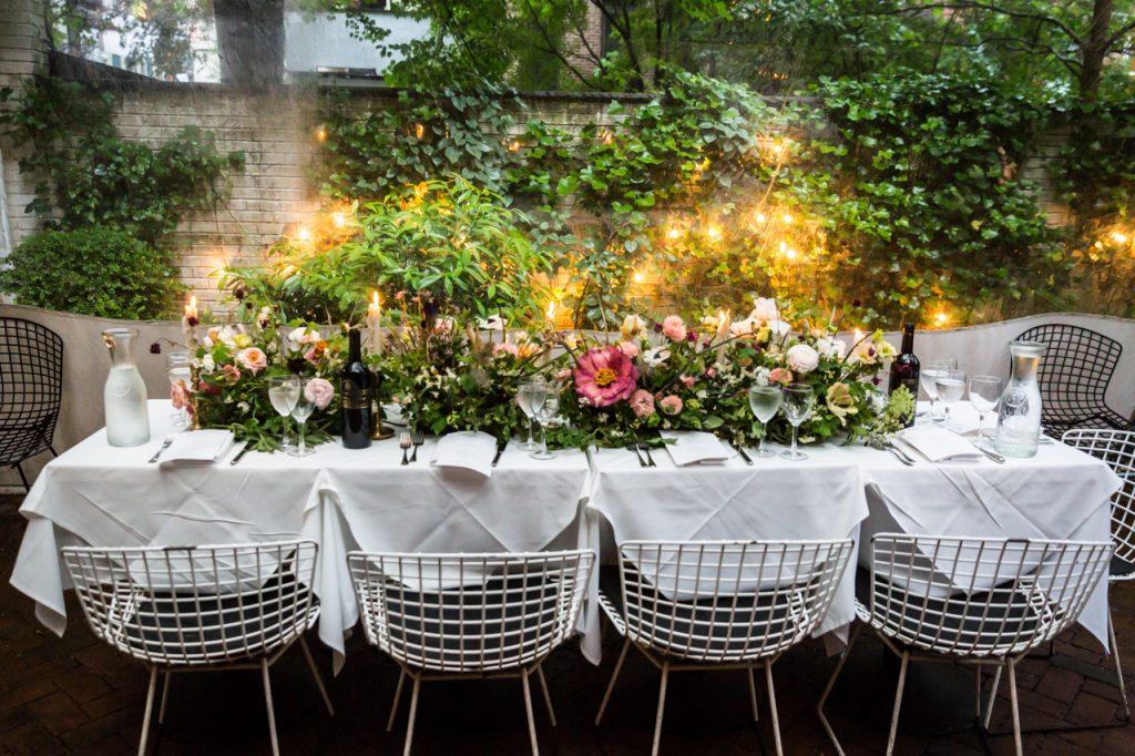 Main table with floral centerpieces at a Central Park Conservatory Garden wedding