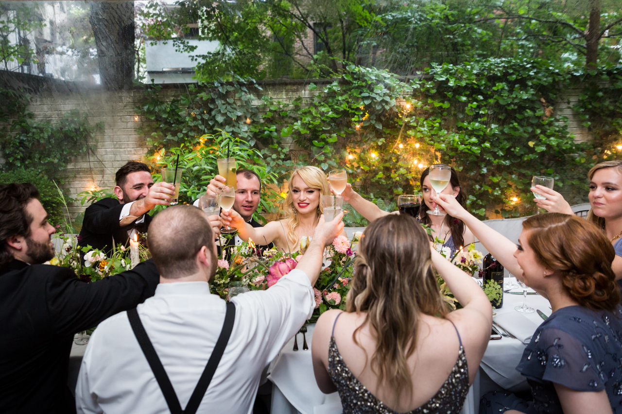 Bridal party toasting glasses at a Central Park Conservatory Garden wedding