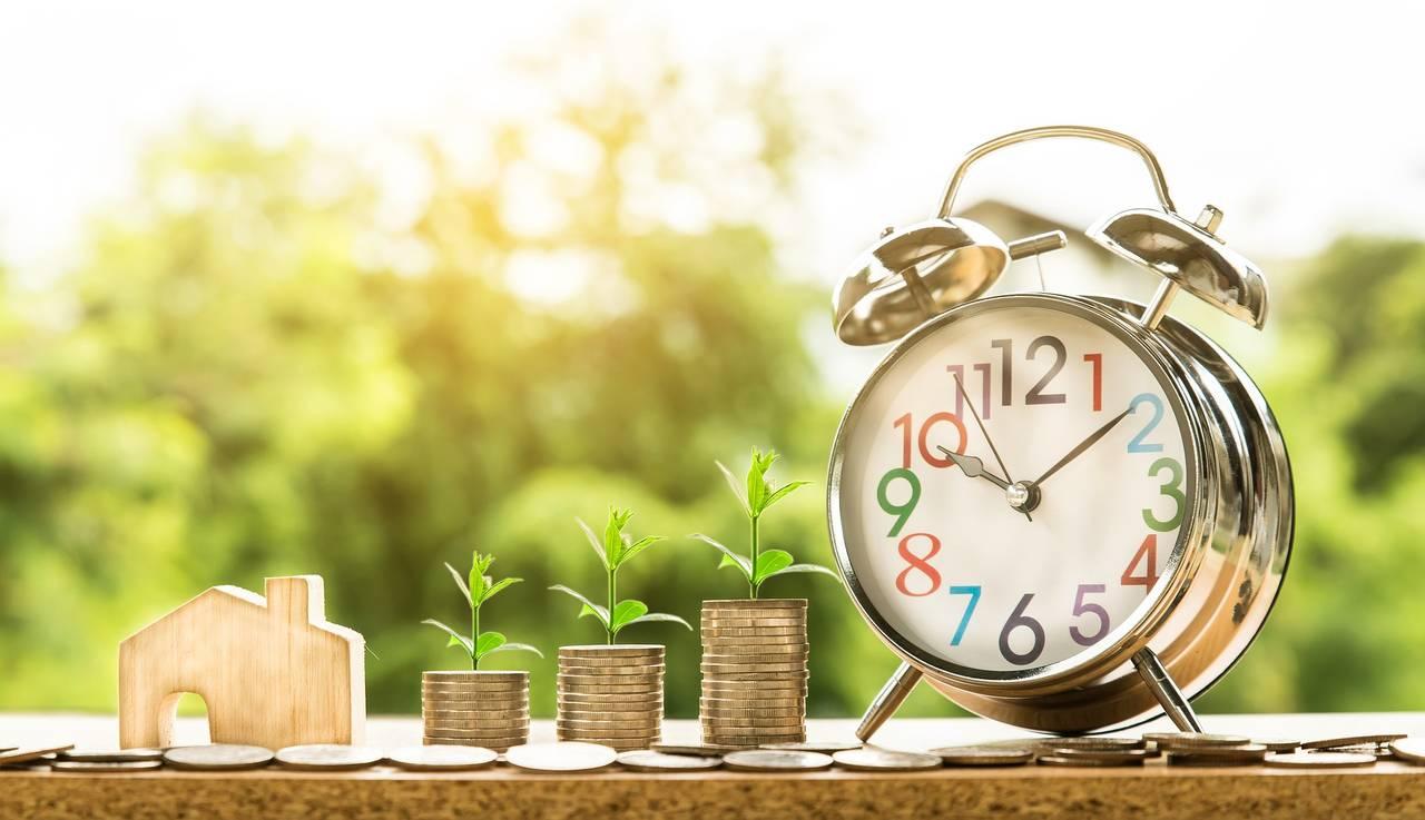 monety oraz zegar symbolizujące czas i pieniądze odłożone na fundusz celowy