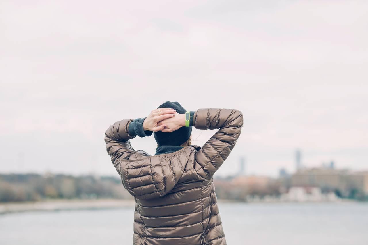 kobieta stoi nad brzegiem rzeki i trzyma ręce na głowie