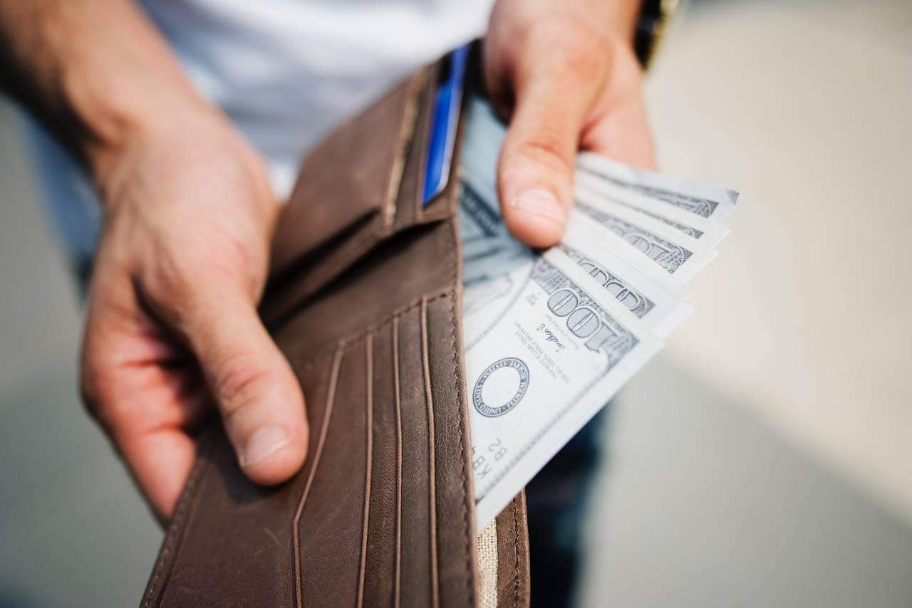 Mężczyzna trzyma portfel pełen gotówki jako symbol zasad racjonalnego wydawania pieniędzy