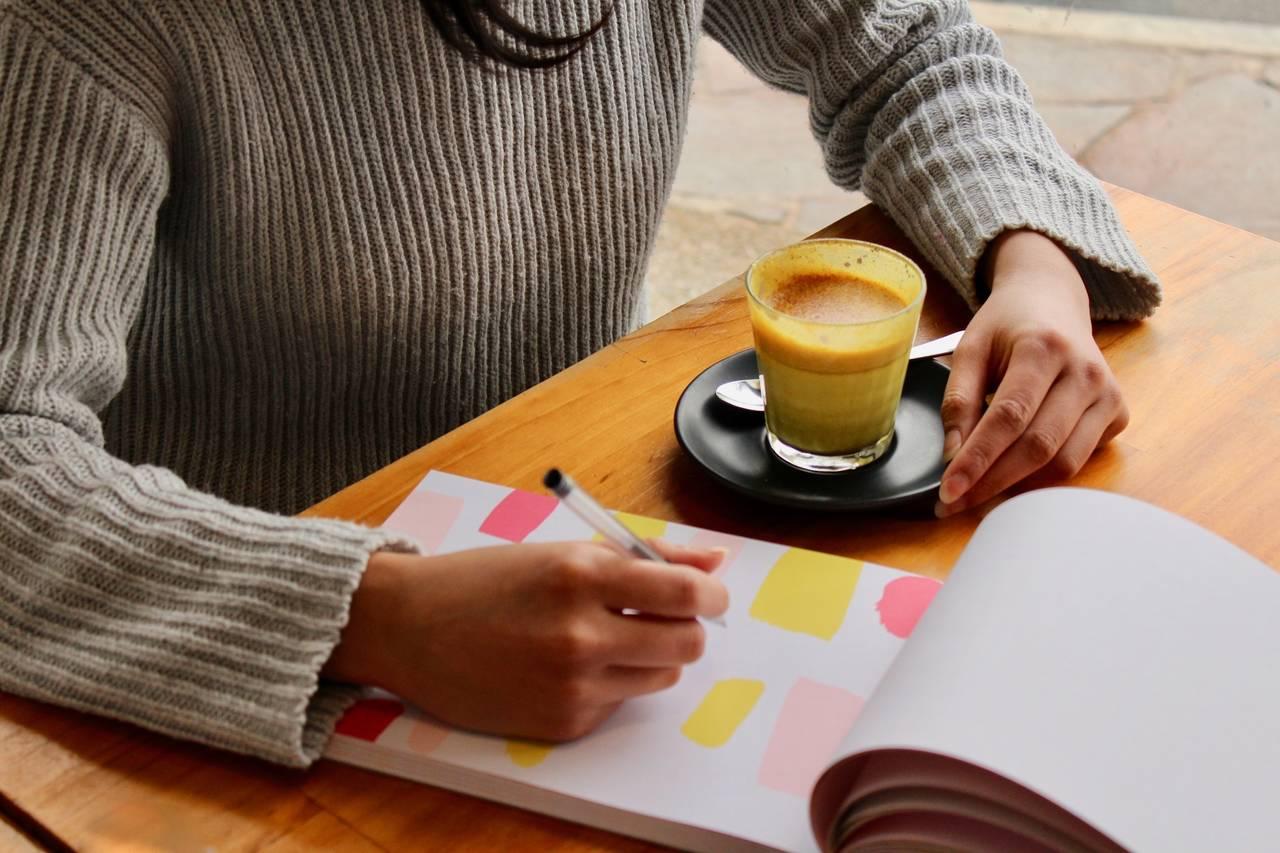 kobieta siedzi nad kartką papieru i zastanawia się jak wyrobić w sobie dobre nawyki finansowe