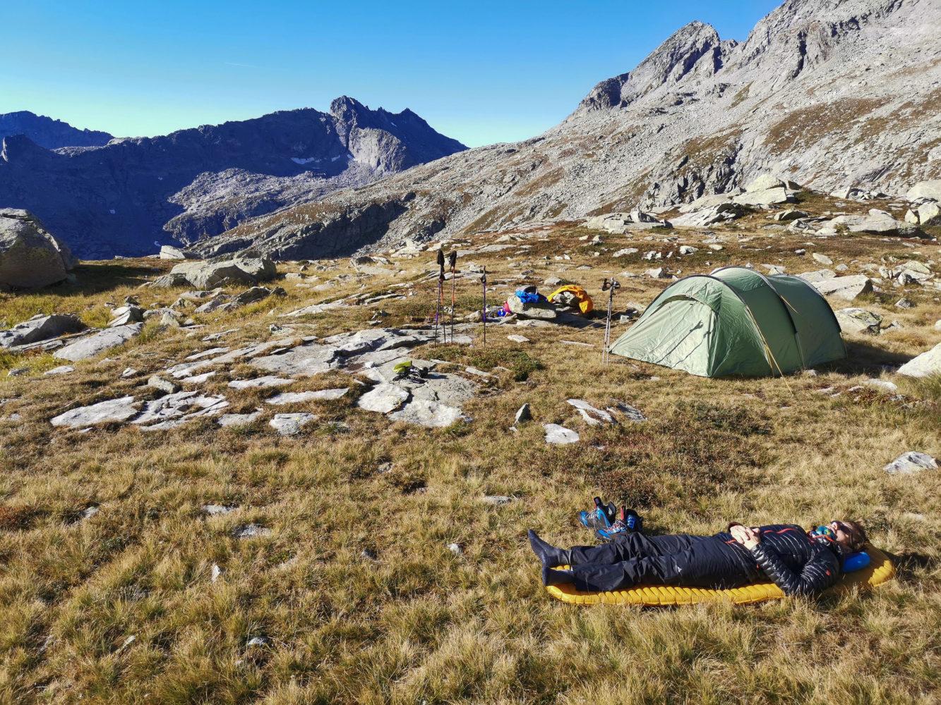 Wanderer liegt auf seiner Isomatte neben seinem Zelt in der Sonne