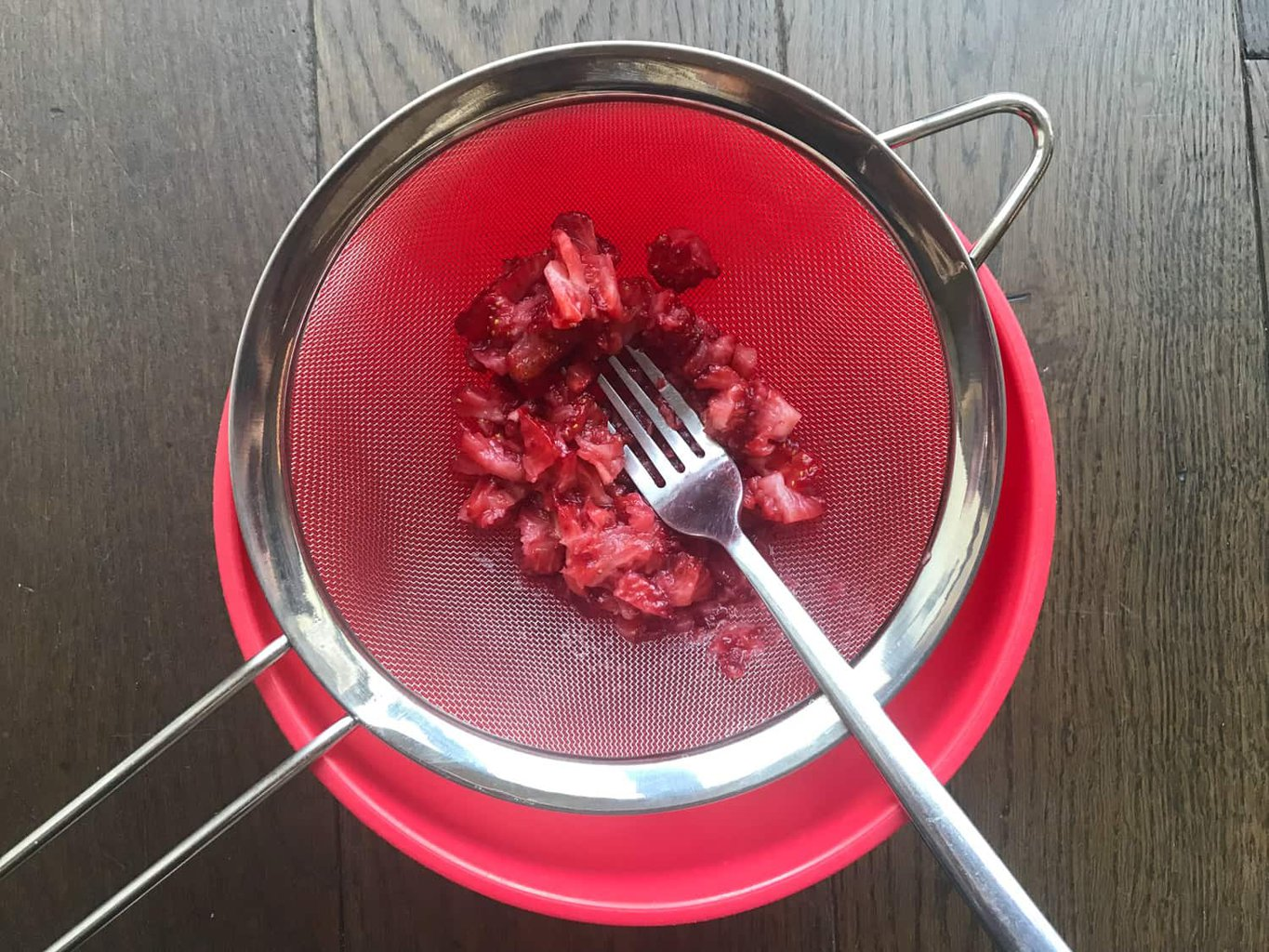 Passing strawberries through a sieve into a bowl