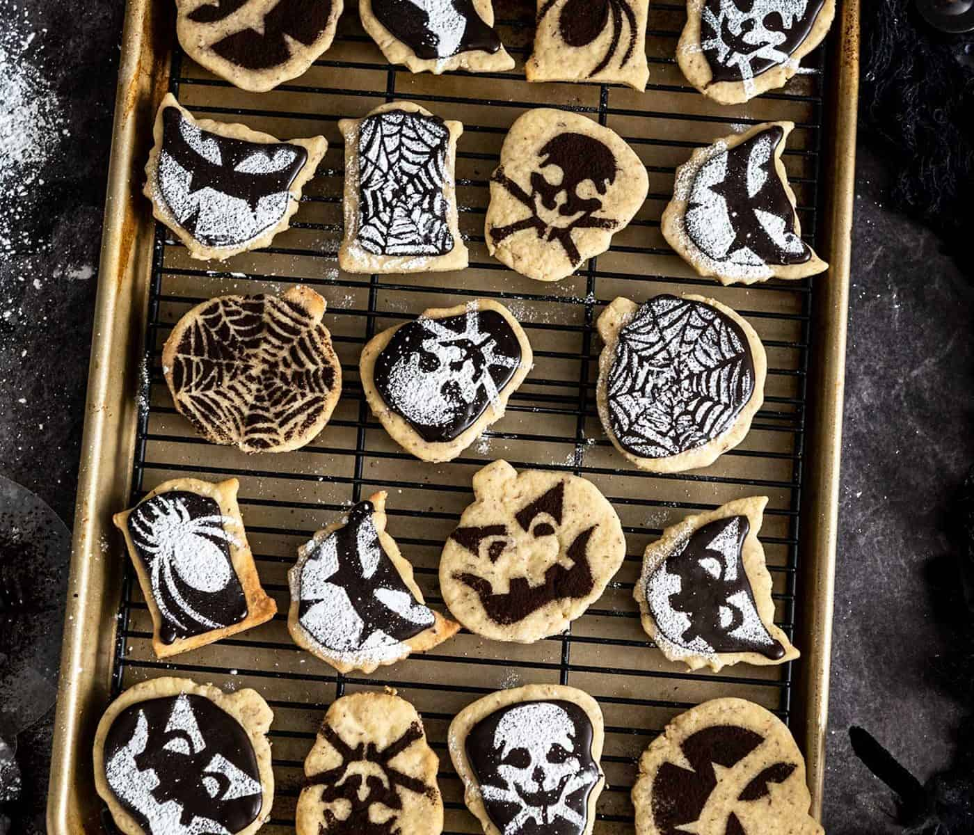 Baking sheet and cooling tray with halloween-stenciled shortbread cookies on it