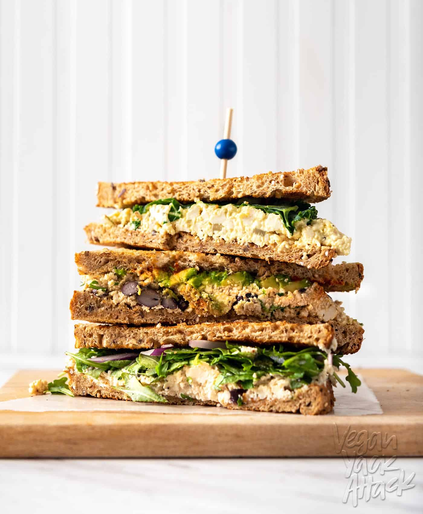 Image of three tofu 'egg' salad sandwiches stacked on one another on a cutting board
