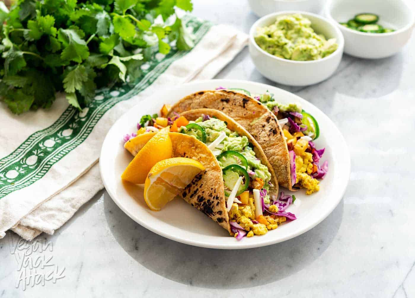 An image of vegan breakfast tacos plated, on a marble table with assorted toppings near it