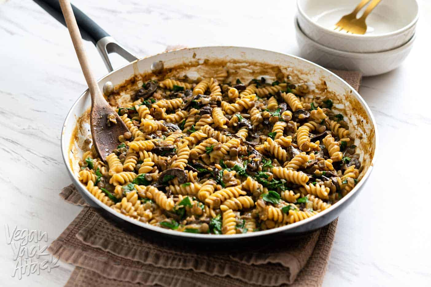 Image of one-pot lentil mushroom pasta in a large pan sitting on a towel