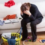 woman sitting with head in her hands near piles of clutter