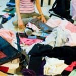 woman sitting on floor surrounded by piles of clothes