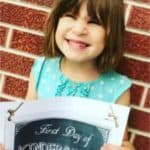 little girl holding first day of school sign