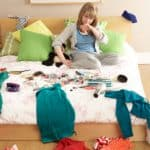 woman sitting on bed in a messy room