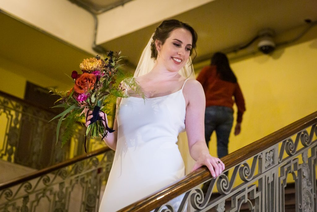Bride holding flower bouquet on staircase looking down