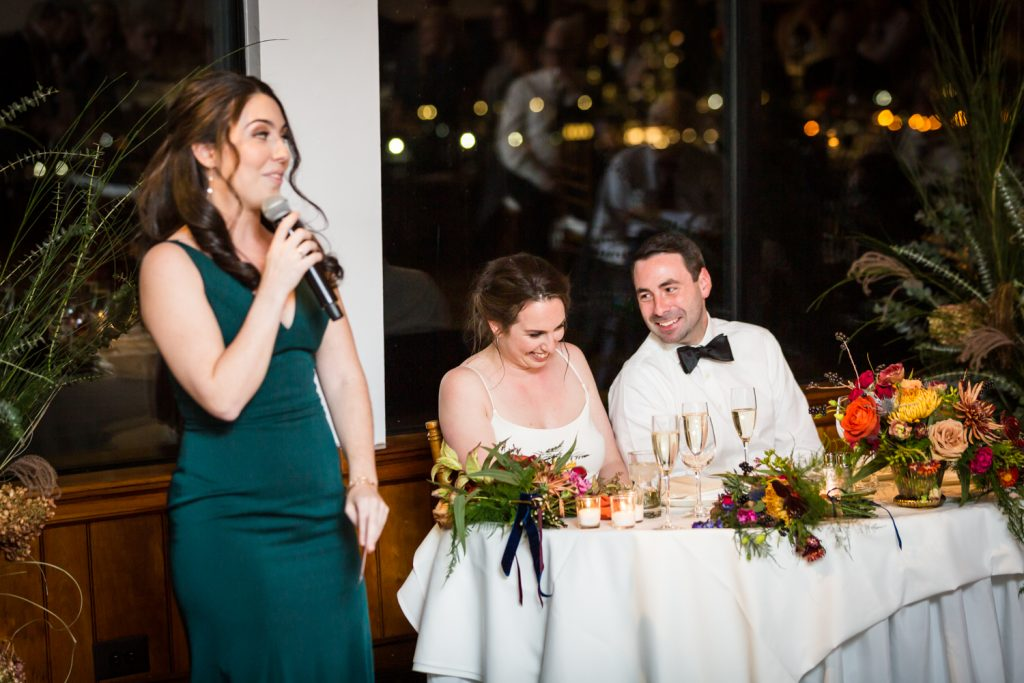 Maid of honor making speech in front of bride and groom