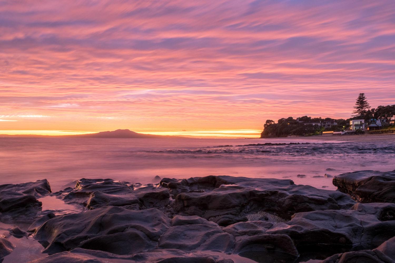 Sonnenaufngang am Milford Beach in Auckland
