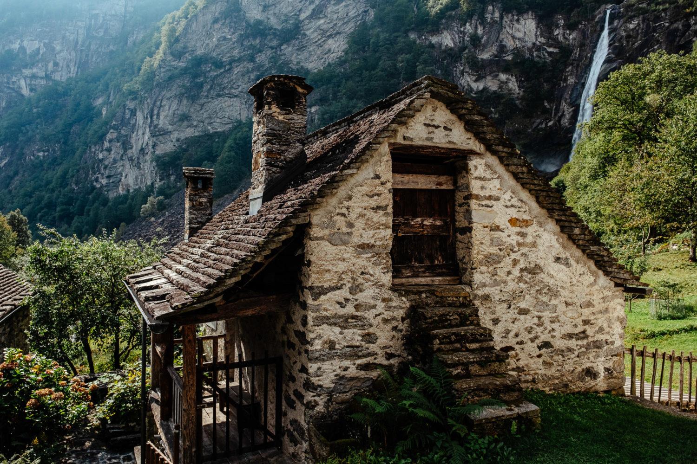 Steinhaus in Foroglio im Val Bavona mit einem Wasserfall im Hintergrund