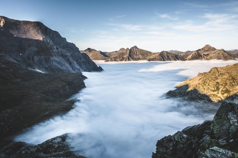 Wolken fließen zwischen Bergspitzen im Val Bavona