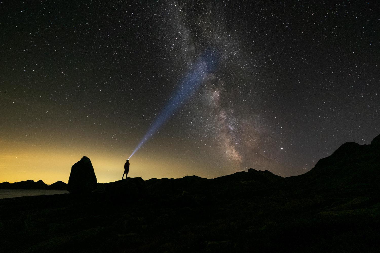 Wanderer mit leuchtet mit Stirnlampe die Milchstraße an
