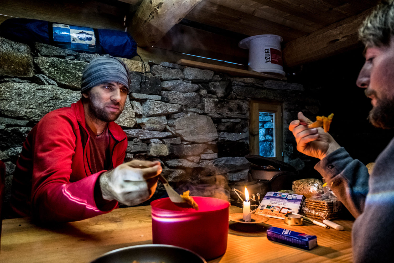Zwei Wanderer essen Nudeln aus einem Topf in einer Steinhütte bei Kerzenlicht