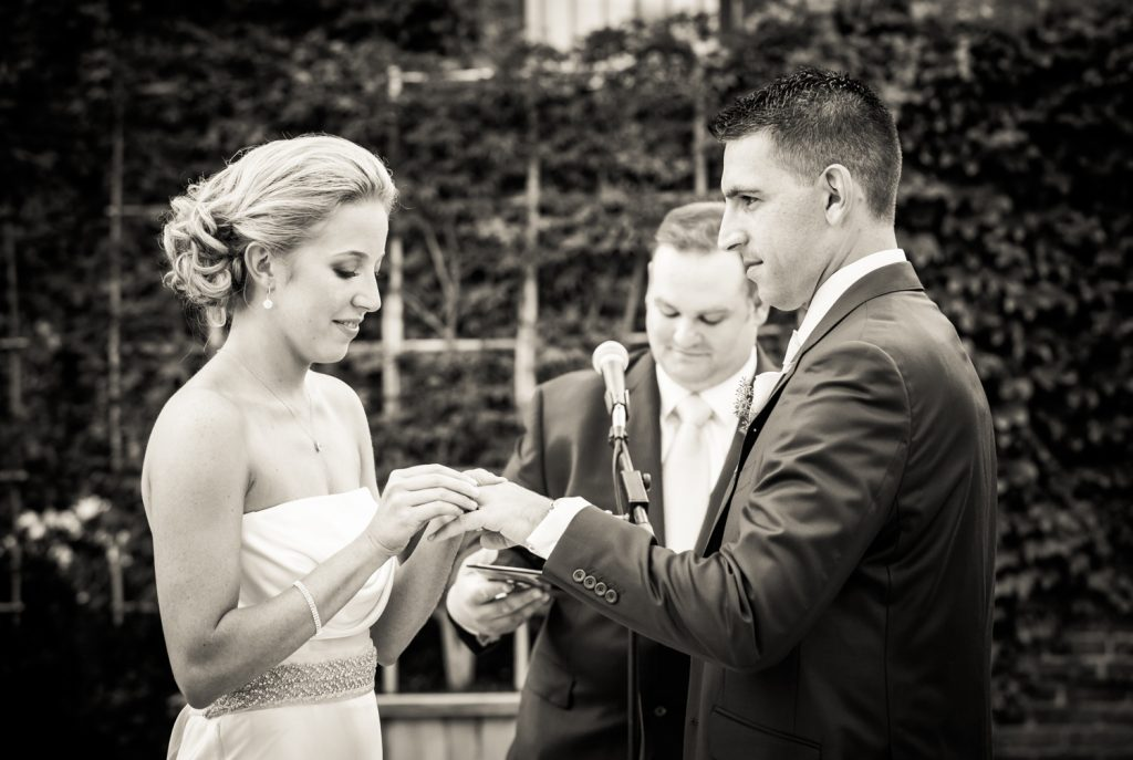 Black and white photo of bride putting ring on groom's finger