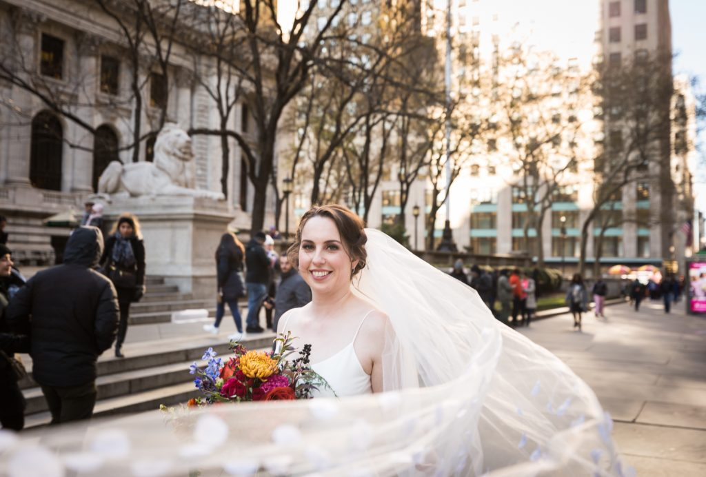 Bride with flowing veil in front of New York Public Library