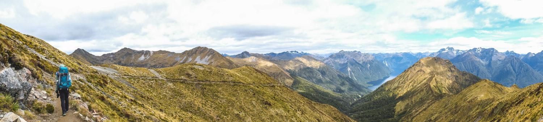 Wandererin auf einem Wanderweg mit Blick ins Tal