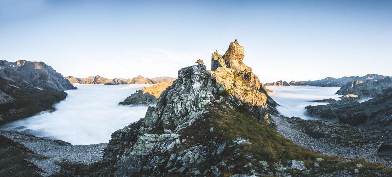Panorama einer Berglandschaft mit Wolken zwischen den Bergspitze