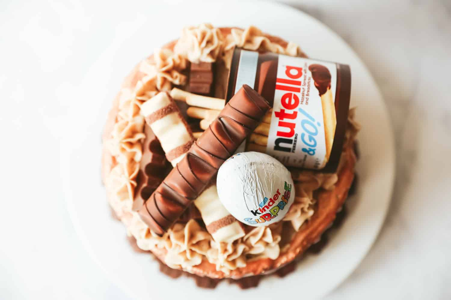 Overhead view of a Kinder cake decorated with a Nutella and Go, a Kinder Egg, Kinder chocolate and Kinder Bueno