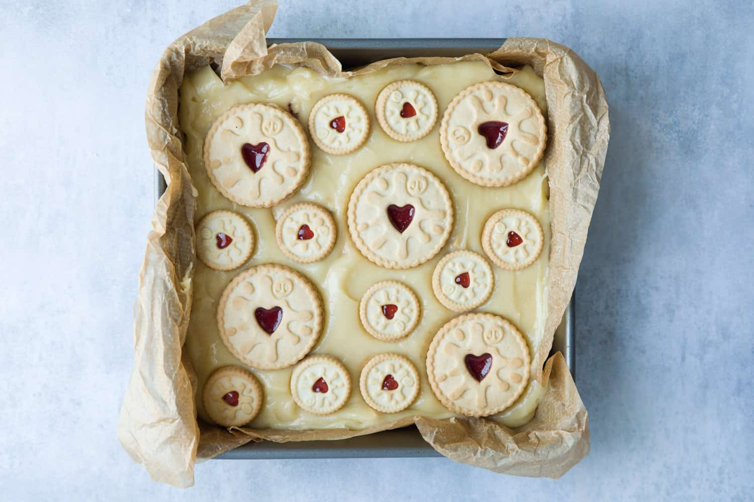 A baking tin with blondie mixture and Jammie Dodgers pressed in to the top.