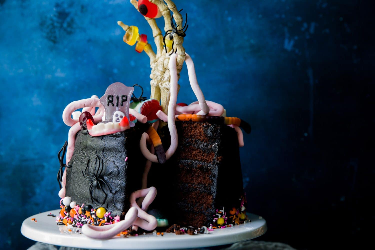 A black Halloween cake that has been cut open to reveal the 5 layers. The cake is topped with a skeleton hand and Halloween sweets.