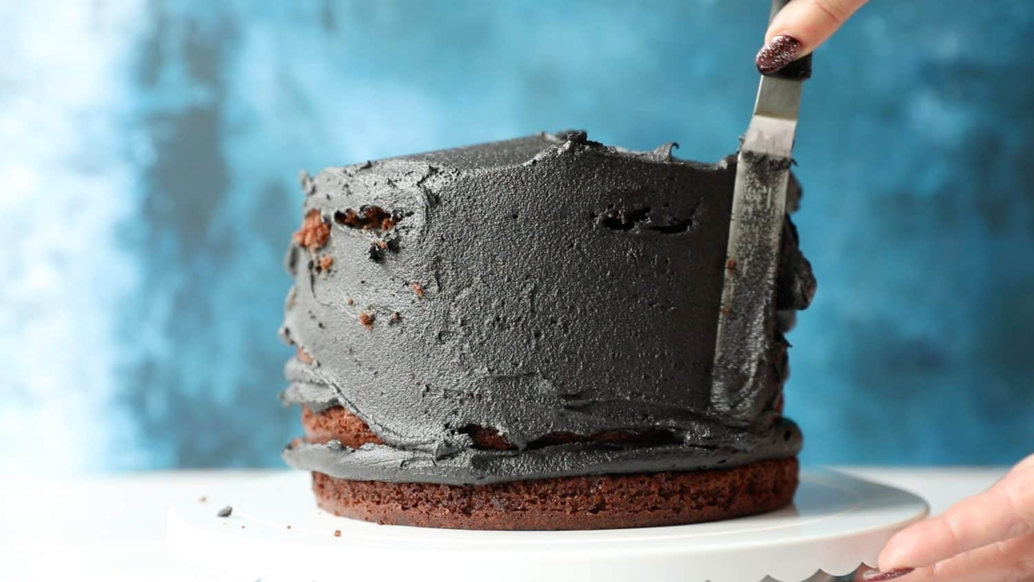 A five layer chocolate cake that has been covered in black buttercream icing. The icing is being spread over the cake using a spatula.
