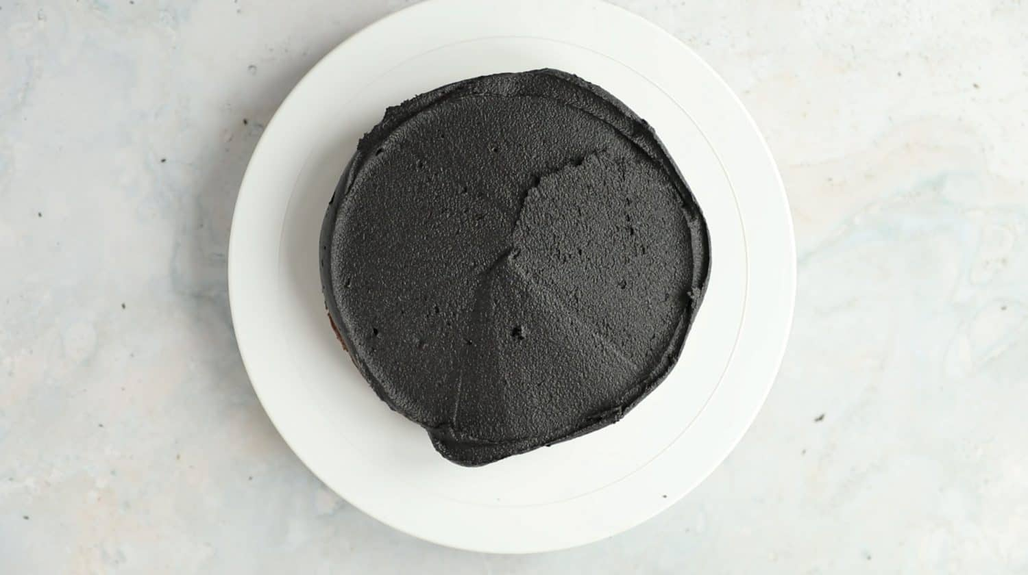 Overhead of a layer of chocolate cake that has had black buttercream icing smoothed over the entire surface.