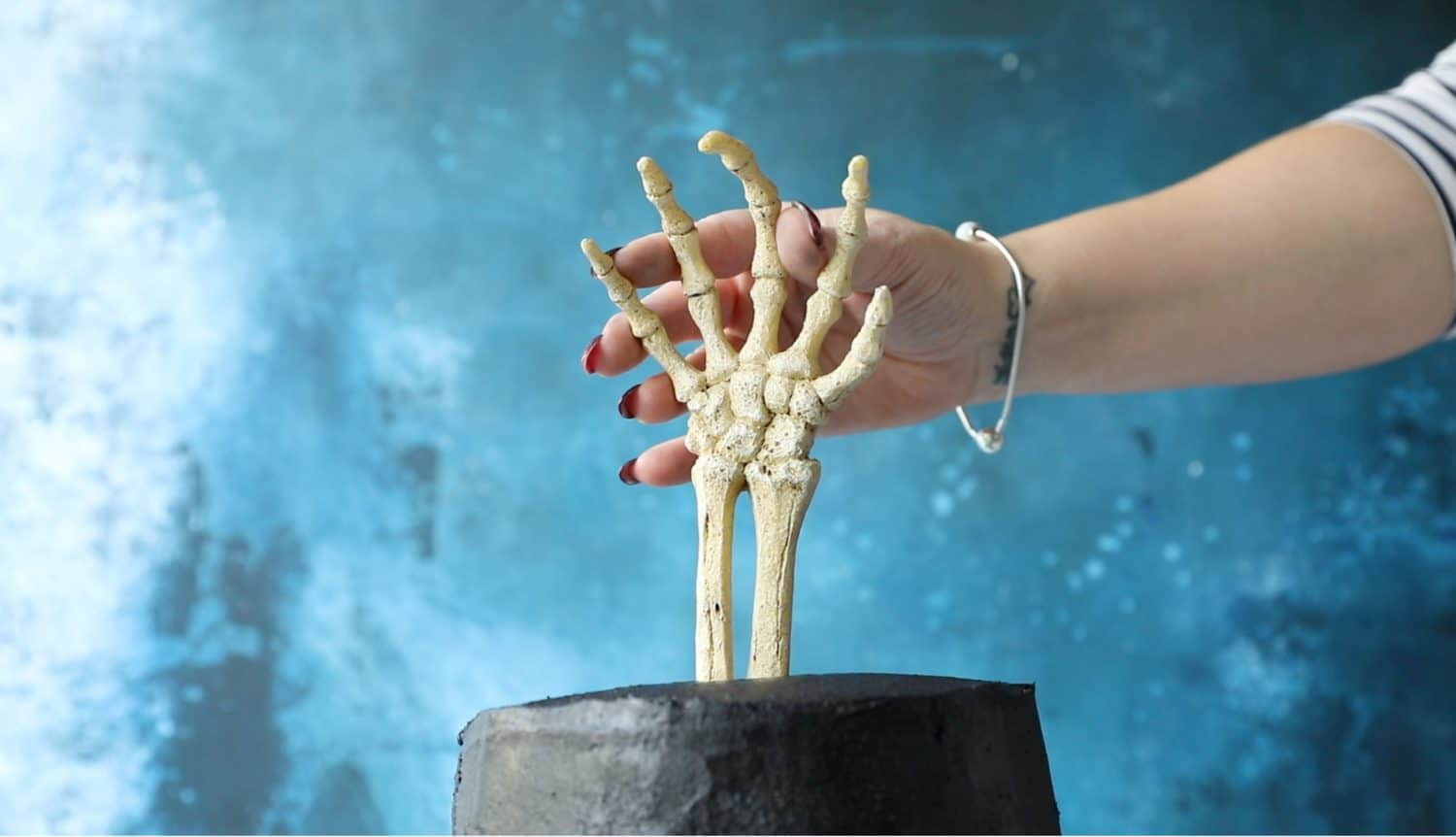 Pushing a skeleton hand into the top of a Halloween cake.